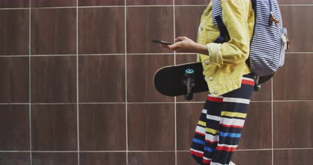 quadris : Side view of mixed race woman out and about in the city on a sunny day, walking using her smartphone carrying her skateboard with brown wall in the background in slow motion. Stock Footage