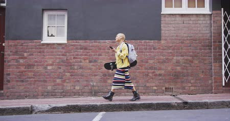 kısa : Side view of mixed race woman with short dyed blonde hair out and about in the city on a sunny day, walking using her smartphone carrying her skateboard with building in the background in slow motion.