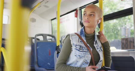 kısa : Front view of happy mixed race woman with short dyed blonde hair out and about in the city on a sunny day, standing on a bus commuting on public transport with earphones on listening to music using her smartphone in slow motion.