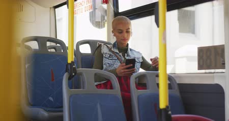 kısa : Front view of happy mixed race woman with short dyed blonde hair out and about in the city on a sunny day, sitting on a bus commuting on public transport using her smartphone in slow motion. Stok Video