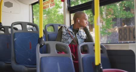 kısa : Side view of happy mixed race woman with short dyed blonde hair out and about in the city on a sunny day, sitting on a bus commuting on public transport with earphones on listening to music looking out of a window in slow motion.