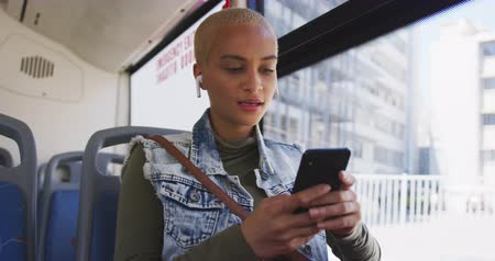 individualidade : Front view of happy mixed race woman with short dyed blonde hair out and about in the city on a sunny day, sitting on a bus commuting on public transport with earphones on listening to music using her smartphone in slow motion. Stock Footage