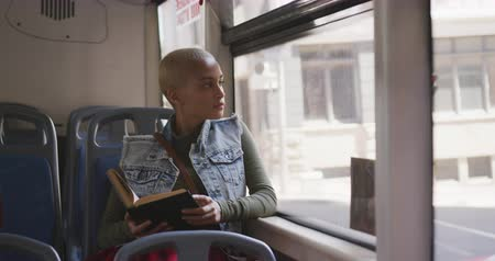 pendulares : Front view of happy mixed race woman with short dyed blonde hair out and about in the city on a sunny day, sitting on a bus commuting on public transport looking out of a window reading a book in slow motion. Vídeos