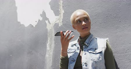 kısa : Front view of happy mixed race woman with short dyed blonde hair out and about in the city on a sunny day, talking on the smartphone leaning against a wall in slow motion. Stok Video