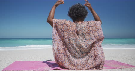 Деятельность выходные : Rear view of a senior African American woman sitting on a beach in the sun, sitting on a yoga mat practicing yoga with hands together in a yoga pose, blue sky and sea in the background in slow motion