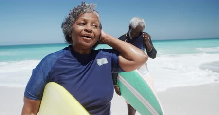 Деятельность выходные : Side view of a senior African American couple on a beach in the sun, carrying surfboards under their arms, with blue sky and sea in the background in slow motion Стоковые видеозаписи
