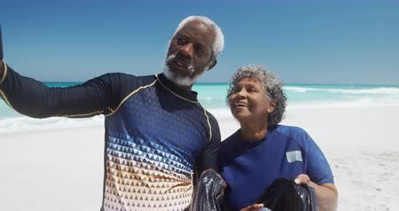odpowiedzialność : Front view of a senior African American couple on a beach in the sun, holding a black rubbish bags and taking selfies, with blue sky and calm sea in the background in slow motion
