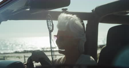 roadtrip : Side view of a senior Caucasian woman on the beach in the sun during a road trip, sitting behind the wheel in the driving seat of a car, wearing sunglasses, smiling in slow motion