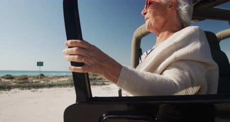 emelt : Side view of a senior Caucasian woman on the beach in the sun, leaning against a car, wearing sunglasses and looking away, smiling in slow motion