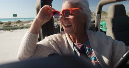 roadtrip : Side view of a senior Caucasian woman on the beach in the sun during a road trip, sitting behind the wheel in the driving seat of a car, wearing sunglasses and looking out of the side window smiling in slow motion