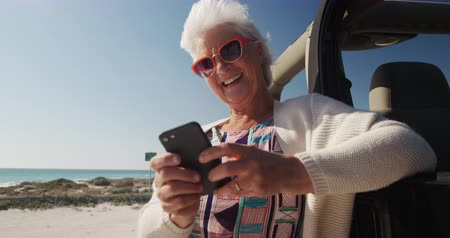 roadtrip : Low angle front view of a senior Caucasian woman on the beach in the sun during a road trip, leaning against a car, wearing sunglasses, smiling and using smartphone in slow motion Stock Footage