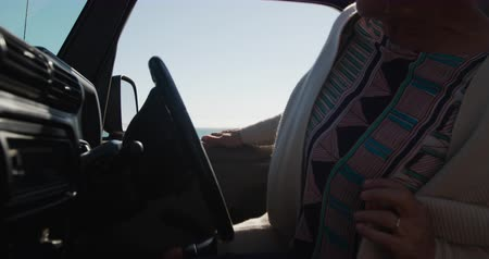Деятельность выходные : Side view of a senior Caucasian woman on the beach in the sun during a road trip, sitting behind the wheel in the driving seat of a car, wearing sunglasses, smiling in slow motion