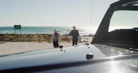 roadtrip : Side view of a senior Caucasian couple on the beach in the sun during a road trip, holding hands and walking, with a car in the foreground in slow motion