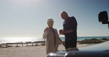 roadtrip : Front view of a senior Caucasian couple on the beach in the sun, using smartphone and standing beside their car during a road trip, using a smartphone and smiling, in slow motion