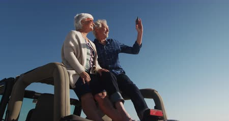 shooting photo : Low angle side view of a senior Caucasian couple sitting on the roof of their car on the beach in the sun during a road trip, man taking photos with smartphone and smiling in slow motion Vidéos Libres De Droits