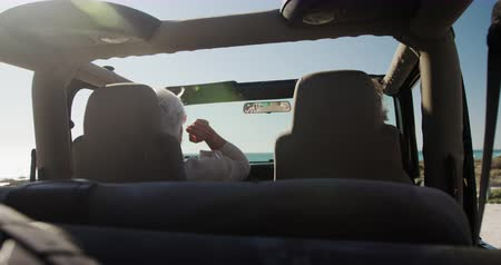 roadtrip : Rear view of a senior Caucasian couple sitting in their car during a road trip, driving to the beach in the sun, the man at the wheel in slow motion