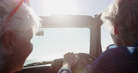 roadtrip : Rear view close up of a senior Caucasian couple sitting in their car during a road trip, driving to the beach in the sun, the man at the wheel in slow motion