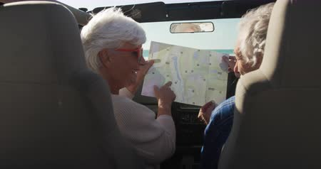 roadtrip : Rear view of a senior Caucasian couple sitting in their car during a road trip, looking at a road map together, the man at the wheel in slow motion Stock Footage