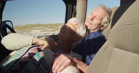 Деятельность выходные : Side view close up of a senior Caucasian couple sitting in their car during a road trip, relaxing and embracing in the sun, in slow motion Стоковые видеозаписи