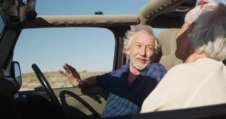 roadtrip : Side view of a senior Caucasian couple sitting in their car during a road trip, the man at the wheel, talking and looking at each other during road trip, smiling in slow motion Stock Footage