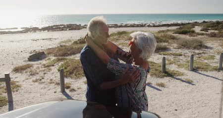 roadtrip : Side view of a senior Caucasian couple in the beach in the sun, standing and embracing, leaning against their car during a road trip, smiling and looking at each other in slow motion