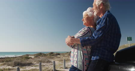 roadtrip : Low angle side view of a senior Caucasian couple on the beach in the sun, standing and embracing, leaning against their car during a road trip, smiling and admiring the view in slow motion