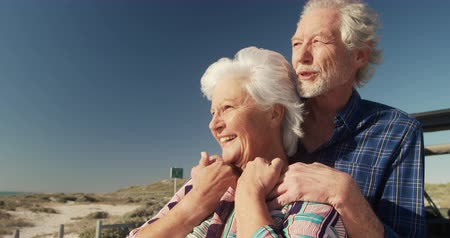 weekendje weg : Side view close up of a senior Caucasian couple on the beach in the sun, standing and embracing, leaning against their car during a road trip, smiling and admiring the view in slow motion Stockvideo