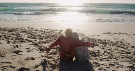 Деятельность выходные : Rear view of a senior Caucasian couple at the beach in the sun, embracing and sitting facing the water, with sea in the background in slow motion