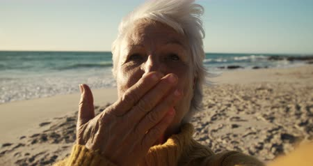 pocałunek : Portrait of a senior Caucasian woman at the beach in the sun, looking to camera and smiling, blowing a kiss, with blue sky and sea in the background in slow motion Wideo