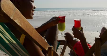 пляжная одежда : Side view close up of a young mixed race man and a young African American woman enjoying free time drinking cocktails and sitting in deckchairs on a sunny beach by the sea