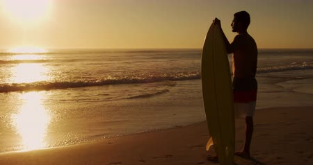 roupa de praia : Side view of a young mixed race man enjoying free time holding a surfboard and watching sunset on a beach by the sea Vídeos
