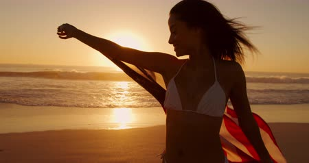bandeira americana : Side view close up of a young mixed race woman enjoying free time running with an American flag on a beach by the sea at sunset