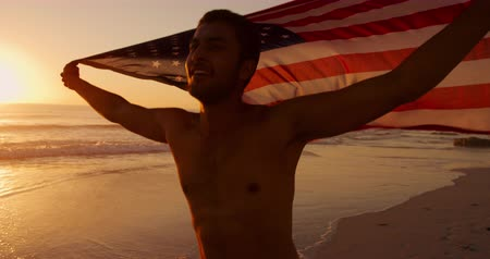 bandeira americana : Side view close up of a young mixed race man enjoying free time running with an American flag on a beach by the sea at sunset Vídeos