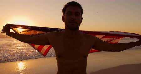 bandeira americana : Front view close up of a young mixed race man enjoying free time running with an American flag on a beach by the sea at sunset Vídeos