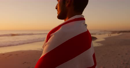 bandeira americana : Portrait close up of a young mixed race man enjoying free time wrapped in an American flag on a beach by the sea at sunset