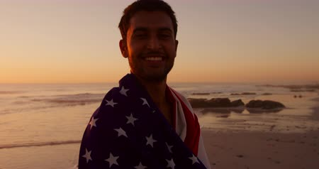 bandeira americana : Portrait of a young mixed race man enjoying free time wrapped in an American flag on a beach by the sea at sunset