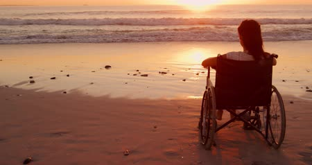 Деятельность выходные : Rear view of a young mixed race woman in a wheelchair enjoying free time watching sunset on a beach by the sea