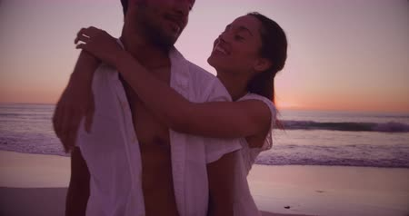 companheiro : Front view of a young mixed race couple enjoying free time embracing on a beach by the sea at sunset