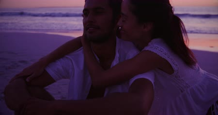 пляжная одежда : Front view of a young mixed race couple enjoying free time embracing on a beach by the sea at sunset