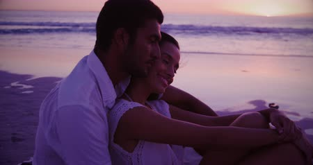 companheiro : Side view of a young mixed race couple enjoying free time embracing on a beach by the sea at sunset