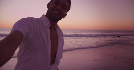 companheiro : Front view of a young mixed race man enjoying free time on a beach by the sea at sunset, holding his partner by her hand