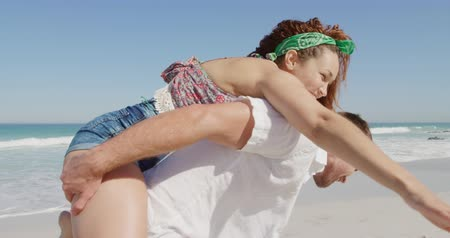пляжная одежда : Front view of a young Caucasian couple enjoying free time on a sunny beach by the sea, the man carrying woman piggyback Стоковые видеозаписи