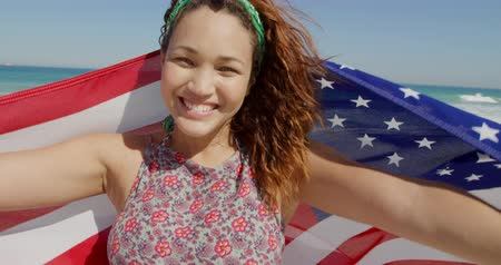 пляжная одежда : Front view of a young Caucasian woman enjoying free time holding an American flag on a sunny beach by the sea
