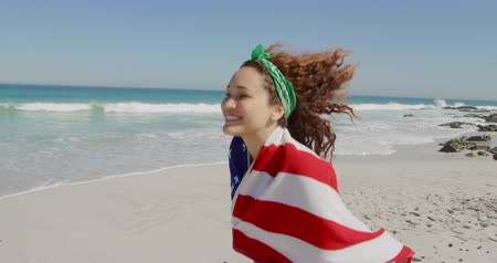 пляжная одежда : Side view of a young Caucasian woman enjoying free time running with an American flag on a sunny beach by the sea Стоковые видеозаписи