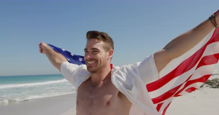 пляжная одежда : Front view of a young Caucasian man enjoying free time running with an American flag on a sunny beach by the sea Стоковые видеозаписи