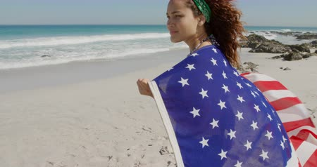 пляжная одежда : Side view of a young Caucasian woman enjoying free time walking with an American flag on a sunny beach by the sea