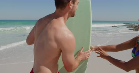 generation z : Side view of a young Caucasian man enjoying free time walking with a surfboard and kissing a young mixed race woman on a sunny beach by the sea