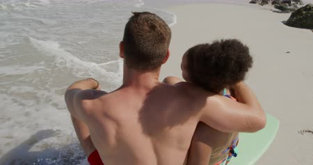 companheiro : Rear view of a young Caucasian man and a young mixed race woman enjoying free time embracing and sitting on a surfboard on a sunny beach by the sea