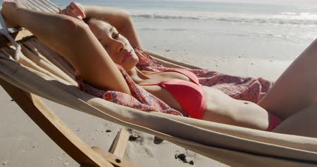 hängematte : Side view close up of a young mixed race woman enjoying free time lying in a hammock on a sunny beach by the sea