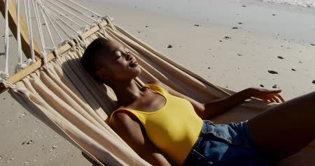 roupa de praia : Side view close up of a young African American woman enjoying free time lying in a hammock on a sunny beach by the sea
